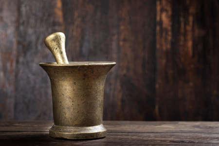 mortaio in ottone per tritare erbe o spezie su fondo in legno. posto per il testo Archivio Fotografico