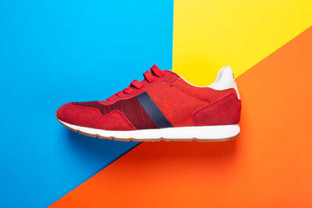 One new fashionable red men's sneakers on a bright background. place for text