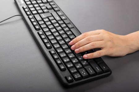 weibliche Hand auf einer schwarzen Computertastatur. Mädchen tippt am Computer