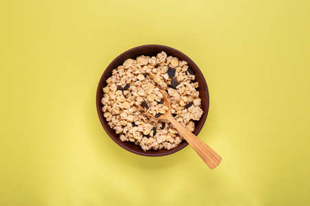 dry granola with nuts and dried fruits in a plate on the table. place for text