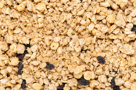 dry granola with nuts and dried fruits sprinkled as a background. place for text