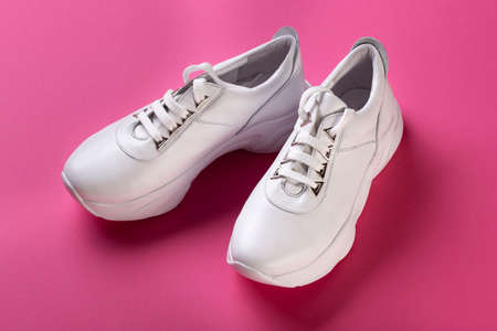 white fashion sneakers on a thick sole, on a pink background. Stock Photo