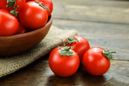 ripe cherry tomatoes in a plate on a brown wooden table. simple rustic background  Banco de Imagens
