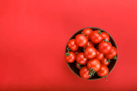 ripe cherry tomatoes in a plate on a bright red background. place for text