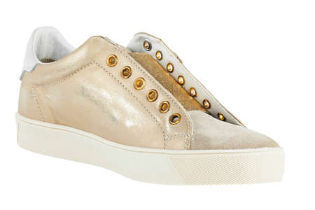 Womens beige sneakers, with a golden sheen. isolated on a white background.