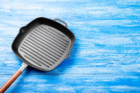 New cast-iron grill pan on a wooden background. place for text
