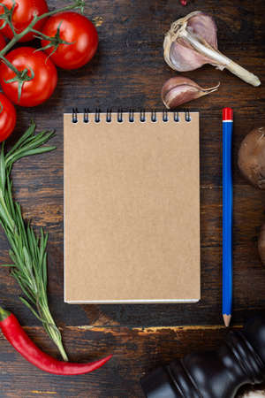 vegetables and a paper notebook on a spiral, on a brown wooden background. place for text Stock Photo