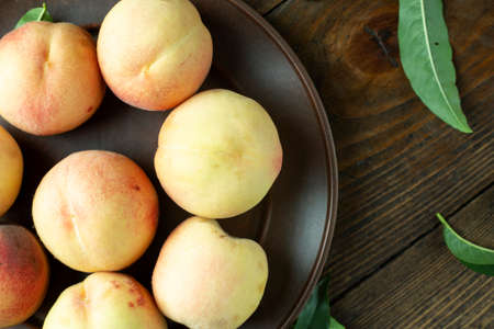 Ripe peaches in  plate on wooden background. Top view.
