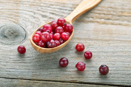 Fresh cranberries in a wooden spoon.