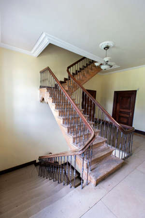 Ancient staircase with iron balusters and wooden railing. Banque d'images