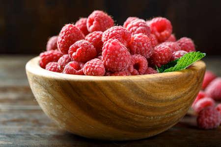 Fresh raspberry in a wooden plate. Healthy berries.