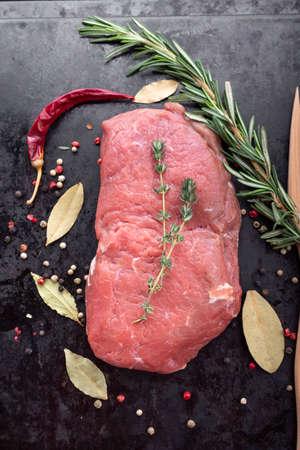 Raw beef steak on a black cutting board with spices. Wood background. 版權商用圖片