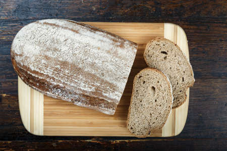 sliced fresh rye bread on a brown wooden background. simple rustic background
