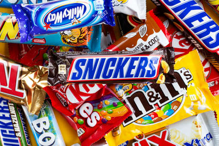 Ukraine, Kyiv - March 23, 2020: A bunch of chocolate bars, including Snickers, Twix, Milka, Kitkat, Lion,  M&M,  Bounty,  on a yellow background. Editöryel