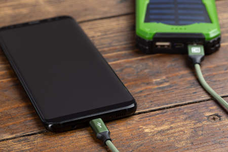 Smartphone charging with power bank on wood board
