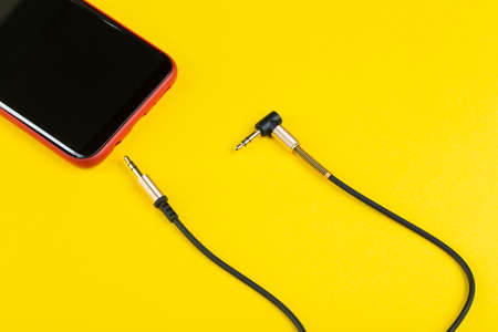 Close-up Jack plug and a cable with phone on a yellow background, top view.