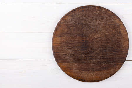 Brown round cutting board on a white wooden background. View from above. Place for text.