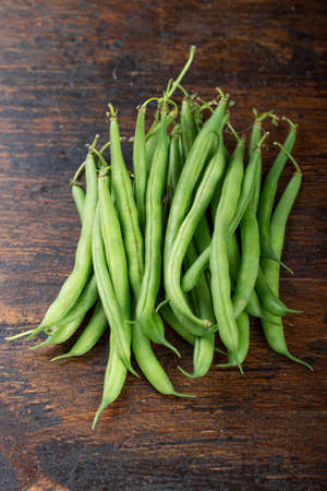Raw fresh asparagus beans, on brown wooden background.