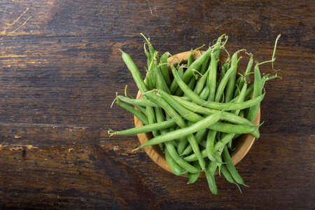 Raw fresh asparagus beans in a plate, on brown wooden background. Stok Fotoğraf