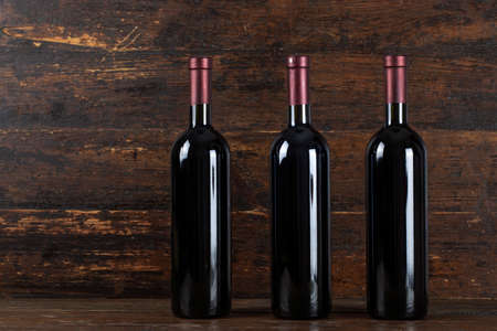 Three red wine bottle on a wooden background.