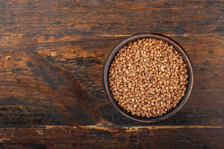 Buckwheat in a clay bowl on a wooden background.