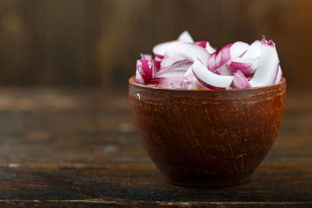 Sliced raw red onion in a bowl on a wooden background. Vegetable, ingredient and staple food. Healthy food. Stockfoto