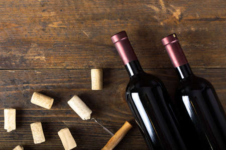 Glass bottle of wine with corks on wooden table background. Top view.