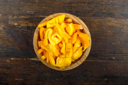 Sliced raw yellow peppers in a bowl on a wooden background. Vegetable, ingredient and staple food. Healthy food. Reklamní fotografie