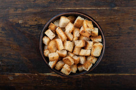 Crispy croutons in a bowl on a wooden background. Top view. Reklamní fotografie