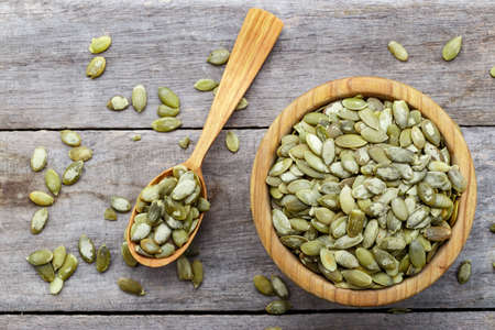 Bowl with pumpkin seeds and a wooden spoon on a wooden table.