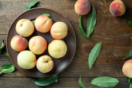 Ripe peaches in a plate on wooden background.