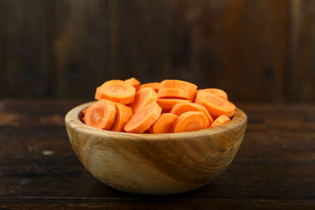 Sliced carrots in a bowl on a wooden background. Vegetable, ingredient and staple food. Healthy food. Reklamní fotografie