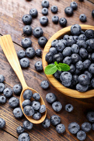 Freshly picked blueberries in wooden bowl on a wooden table. Healthy fruits. Blueberry antioxidant.