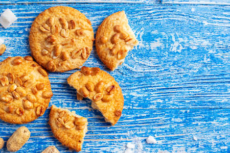 homemade shortcrust pastry sprinkled with peanuts. scattered on a blue wooden background