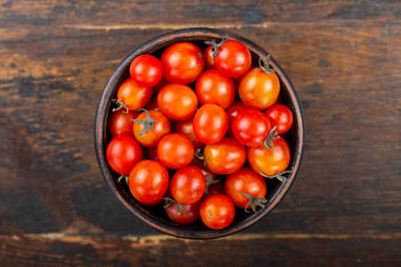 red cherry tomatoes in a plate on a wooden background. place for text
