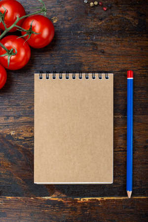 vegetables and a paper notebook on a spiral, on a brown wooden background. place for text