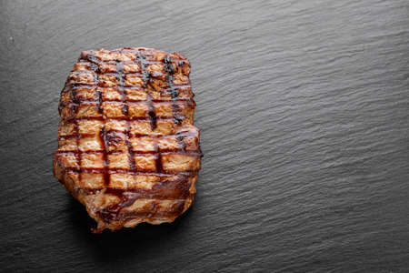 Grilled beef steak on a slate board. Space for text.