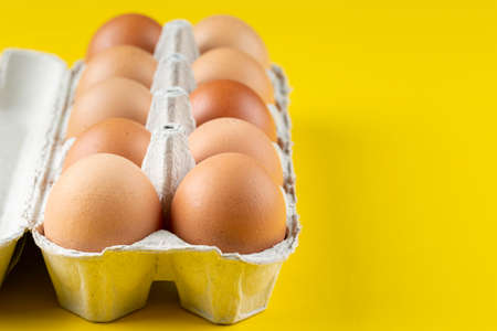 Brown eggs in box on yellow background. Reklamní fotografie