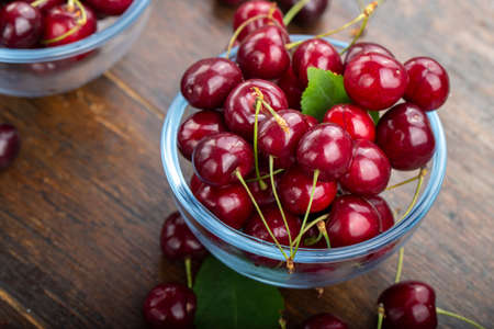 Sweet cherry in a plate on a wooden table.