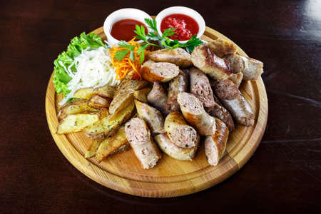 A dish of delicious homemade sausage is cut on a cutting board. next is the sauce in the gravy boats Reklamní fotografie