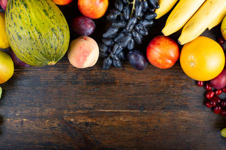 different fresh fruit set. on a wooden brown background. place for text