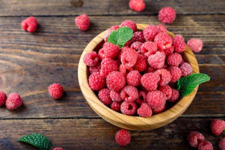 fresh raspberries on a wooden background, in a simple wooden plate. organic summer crop