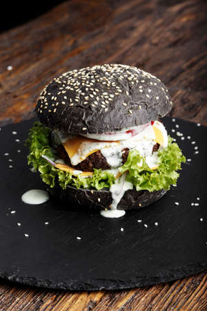 Fresh black burger with meat and vegetables, sprinkled with sesame seeds. on a black slate board
