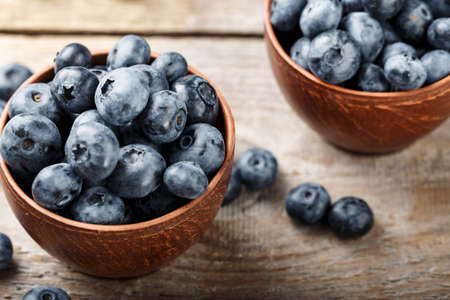 ripe blueberries in a clay plate on a brown wooden background. place for text