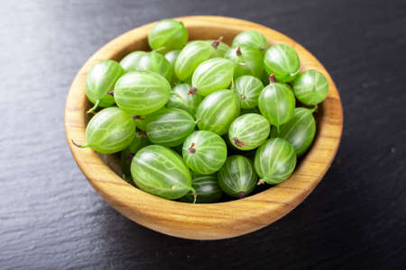 Fresh gooseberries in wooden bowl on black stone slate background. Top view.