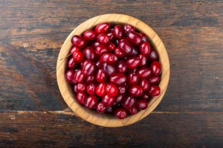 Dogwood in a plate on a wooden background. Gathering the summer harvest. Red berry. Top view.