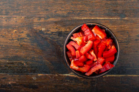 Sliced raw red bell pepper in a bowl against a wooden background. Vegetable, ingredient and staple foods. Useful food.