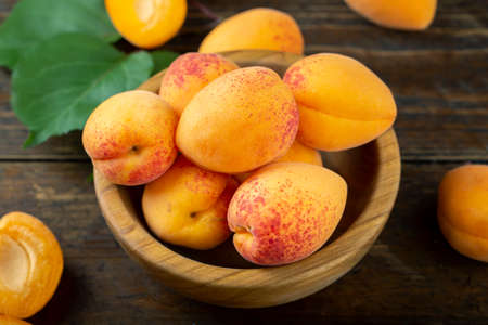 Delicious ripe apricots in a wooden bowl on the table close-up.