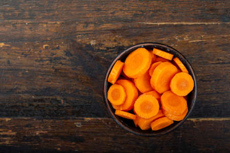 Sliced carrots in a bowl on a wooden background. Vegetable, ingredient and staple food. Healthy food. Фото со стока