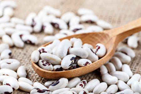 raw black-eyed beans sprinkled on a wooden background and scooped into a spoon. place for text